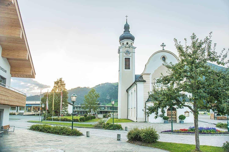 Gemeindeamt mit Dorfplatz und Pfarrkirche im Hintergrund